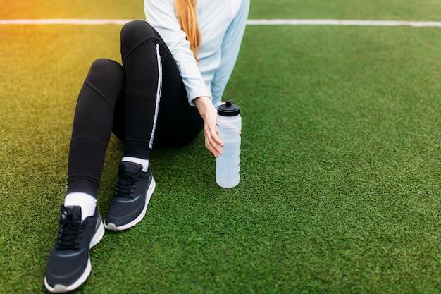 良いトレーニングの後休んでいる女の子。運動後、サッカー場で水を飲む女の子。スポーツウェアの美しい少女の肖像画。