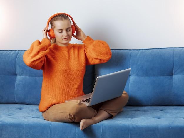 Девушка отдыхает дома в наушниках за компьютером