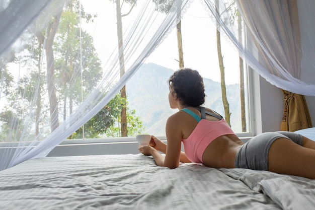 Girl resting and drinking tea in bed with a view of the mountain on the island sri lanka