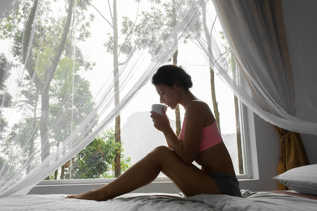 Girl resting and drinking. tea in bed with a view of the mountain