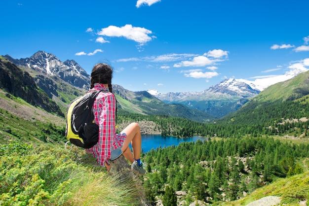 湖の景色を眺めながら山でのトレッキング中に休んでいる女の子