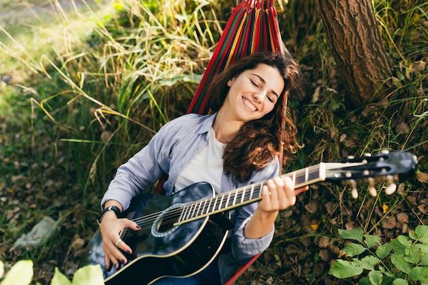 Девушка отдыхает в парке с гитарой в гамаке