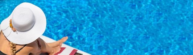 帽子をかぶってプールの近くで休んでいる女の子。セレクティブフォーカス。女性。