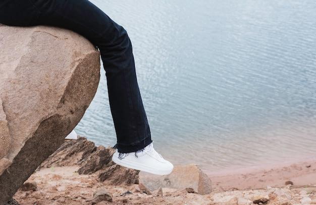 Девушка отдыхает на скале. женщина сидит на скале у реки.