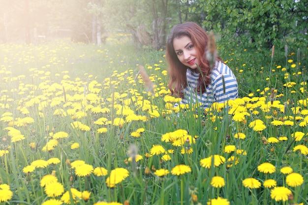 노란 민들레 풀밭에서 화창한 날 쉬고 있는 소녀