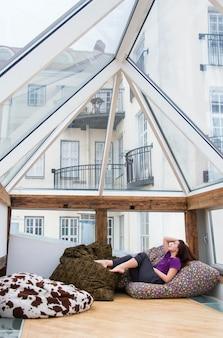 Девушка отдыхает на подушках на террасе