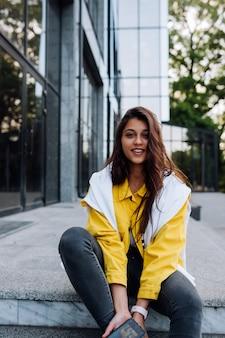 ステップで休んでいる少女。街の通りを歩いて魅力的なファッショナブルな陽気なトレンディな内気な少女。