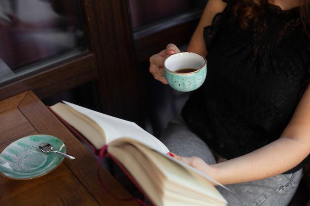 本を読んでコーヒーを飲みながら休んでいる女の子
