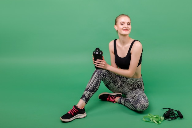 Girl rests after workout with water bottle, rope