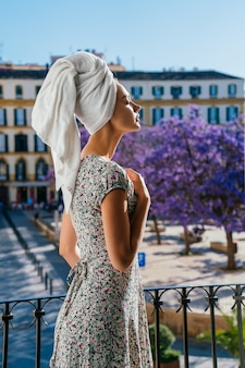Girl in retro dress enjoys the weather on the balcony. european city background