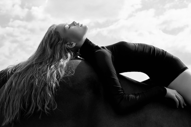 Girl rider lies bent on a horse in the field. fashion portrait