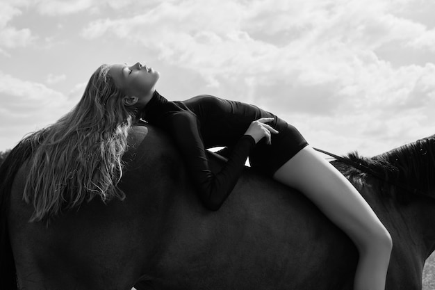 Girl rider lies bent on a horse in the field.