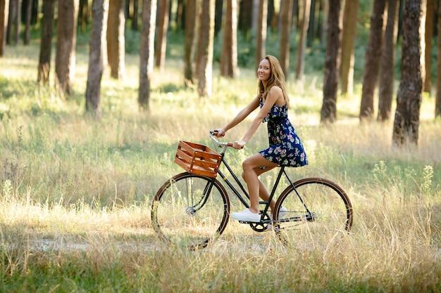Девушка едет на велосипеде с корзиной в лесу.