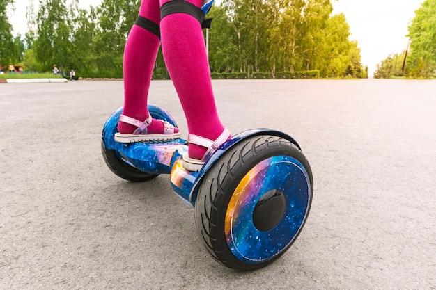 소녀는 자이로 스쿠터를 탄다. 분홍색 팬티 스타킹과 샌들을 신은 어린 소녀의 발이 자이로 스쿠터에 있습니다. 자기 균형 스쿠터