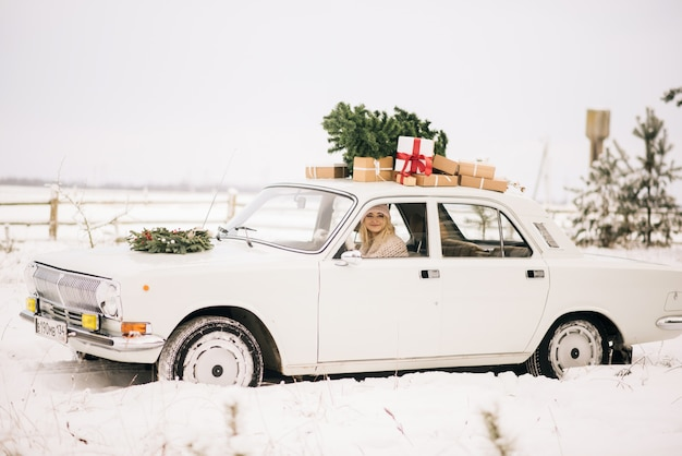 The girl rides in a retro car decorated with a christmas tree and presents in a snowy forest. the concept of a winter christmas photo shoot