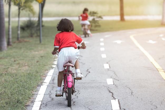 アスファルト道路上の交通規則で自転車に乗っている少女