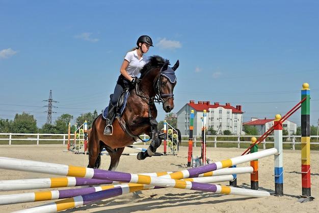 馬に乗っている女の子は、トレーニングの障壁を飛び越えます。