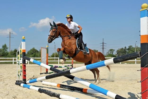 Девушка верхом на лошади на соревнованиях по прыжкам в воду