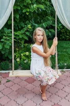 庭の夏にブランコに乗っている女の子