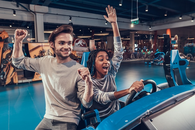 Girl riding car in arcade. guy is helping. girl is winning.