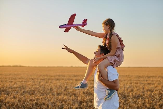 아버지의 어깨에 타고 장난감 비행기를 가지고 노는 소녀