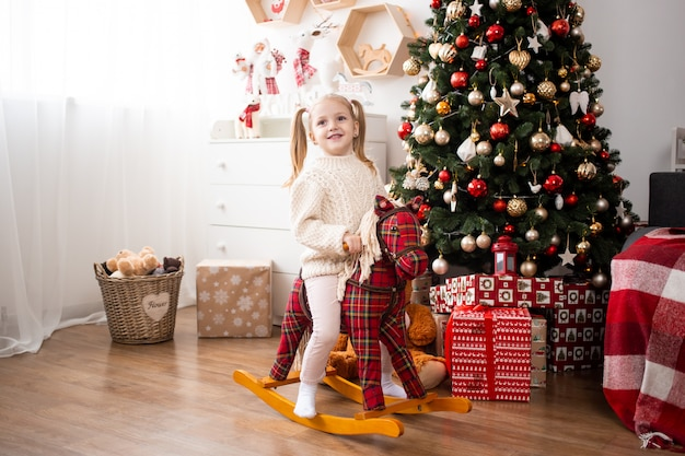 Girl riding toy horse at home near christmas tree and gift boxes