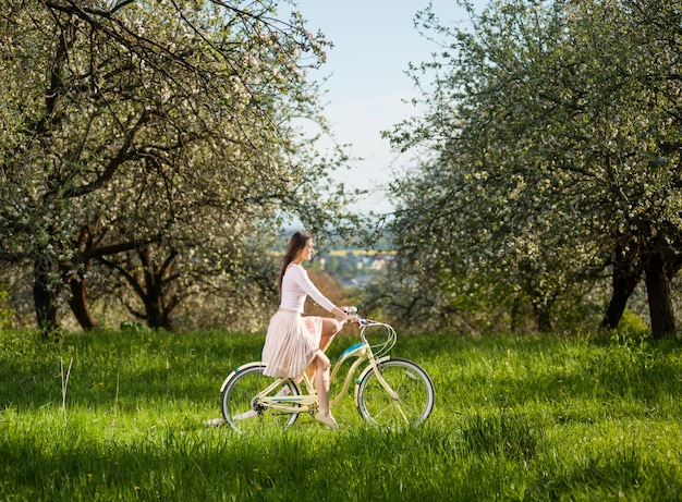 Girl riding a vintage white bike in the spring garden at the sunny day