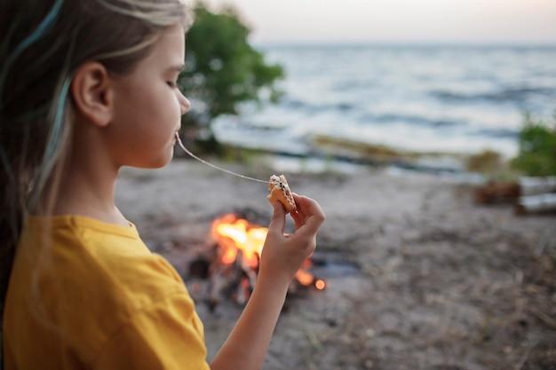 キャンプの伝統的な旅行の食べ物の間に火の炎の上でスモアを作るためにマシュマロを焼く女の子