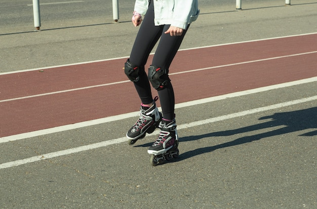 A girl roller skates on a bicycle path in the city in the summer. summer holidays in the city and an active lifestyle.