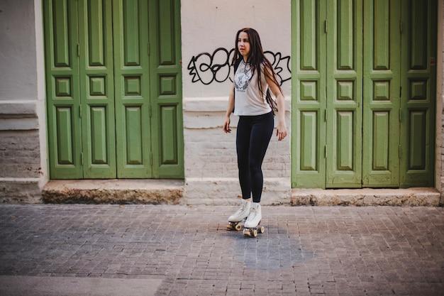 Girl in rollerskates standing on street