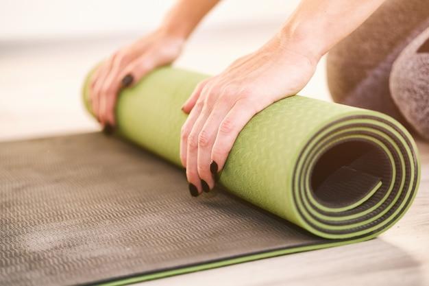 Девушка скатывает спортивный коврик руками по полу - спортивный коврик для тренировок - фитнес, спорт и концепция ухода за собой - здоровый образ жизни