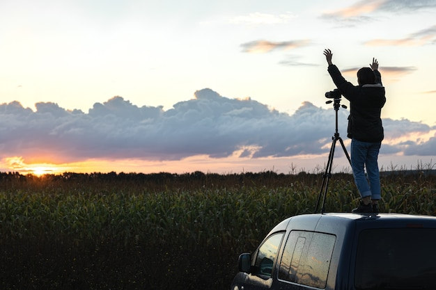 The girl on the roof of the car photographs the sunset with a tripod.