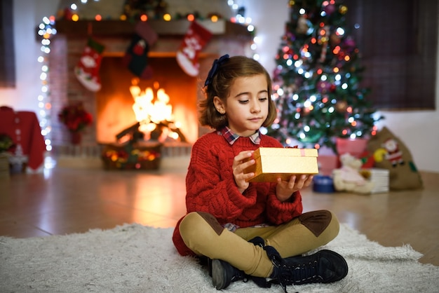 Ragazza in una sala decorata per natale con confezione regalo d'oro