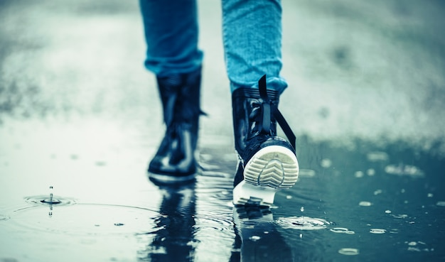 Girl in rubber boots outdoors in rainy day.