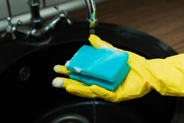 A girl in rubber gloves holds a sponge for washing dishes