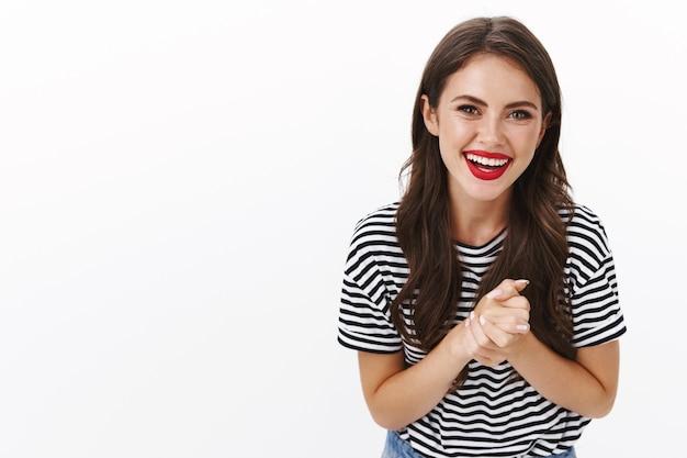 女の子はかなり手をこすり、感謝の友人の助け、面白がって楽しい笑顔を喜んで立ち、縞模様のtシャツ、赤い口紅を着て、素敵な面白い会話を楽しんで笑って、白い壁