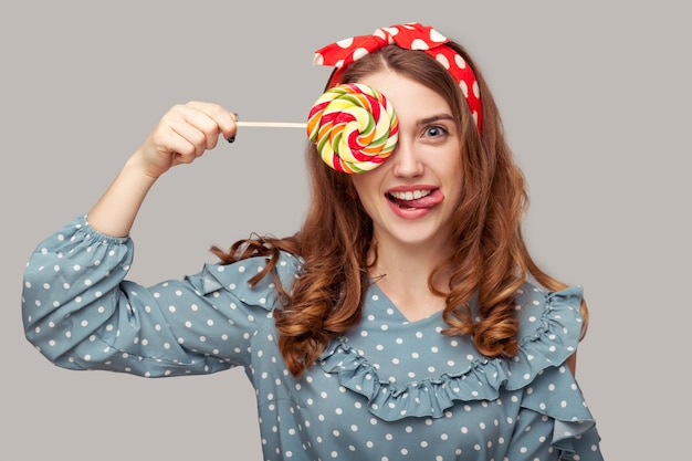Girl ruffle blouse covering eye with sweet spiral candy looking at camera showing tongue out