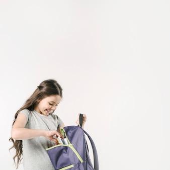 Девушка рыться в рюкзаке в студии