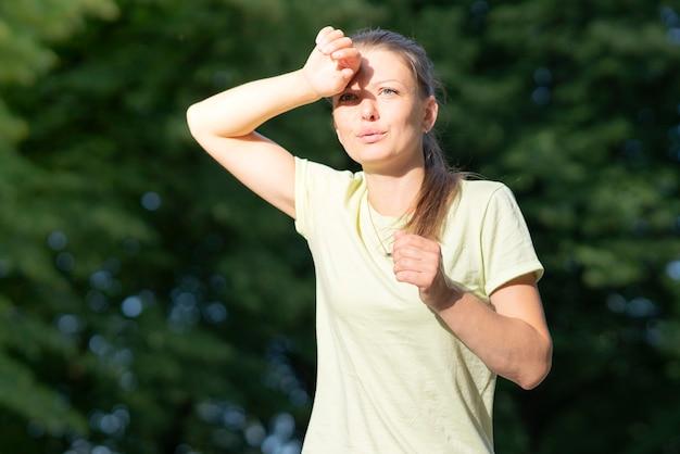 소녀 러너는 달리기, 조깅 시 통증을 겪고 있습니다. 더위, 열사병에 걸린 여자. 여름 더운 날씨에 일사병이 있습니다. 위험한 태양, 햇살 아래 소녀. 두통, 기분 나쁨, 피곤함, 지쳐