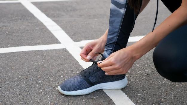 公園の道路で靴をジョギングするために靴ひもを結ぶ女の子のランナー。スポーツライフスタイル。