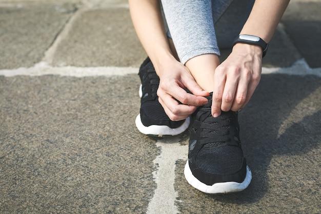 公園の道路で靴をジョギングするために靴ひもを結ぶ女の子のランナー