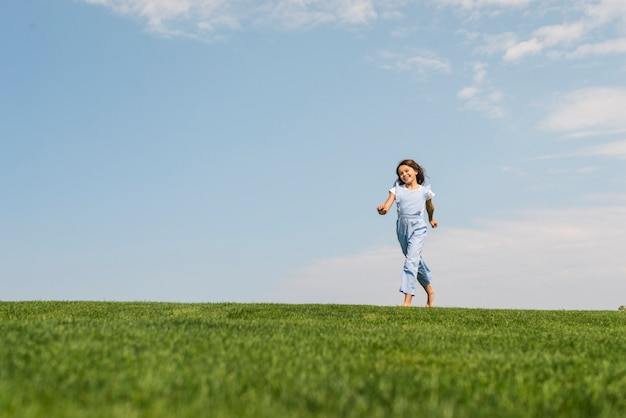 Girl running barefoot on grass