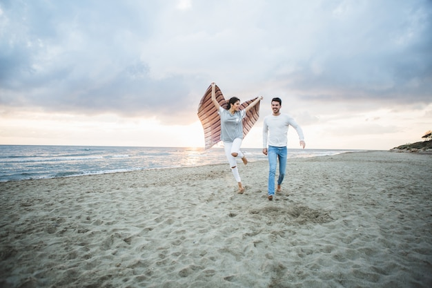 Girl running on the beach with a blanket and her boyfriend next to