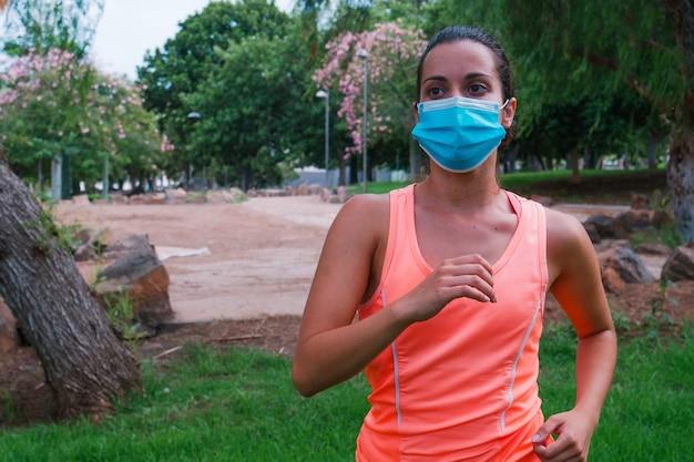 Covid19検疫の真ん中にマスクを持って公園を走っている女の子