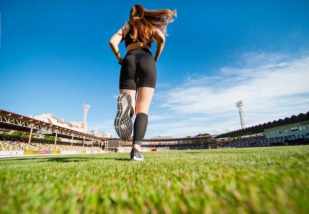 実行している女の子、足をクローズアップ、後ろからの底面図