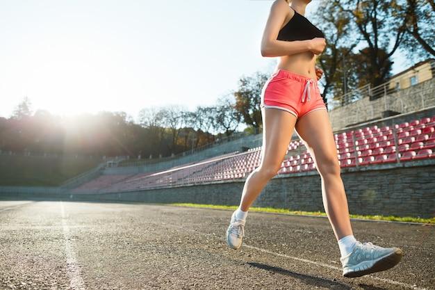 スタジアムでトラックを実行している女の子。黒のトップ、ピンクのショートパンツと白のスニーカーの若い女性。アウトドア、スポーツ、顔なし