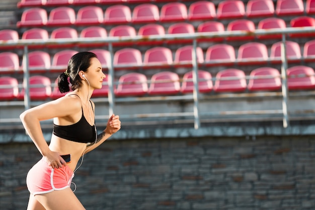 Girl running track on stadium and listening to music. profile of young woman in black top and pink shorts running and holding phone. outdoors, sport, copyspace