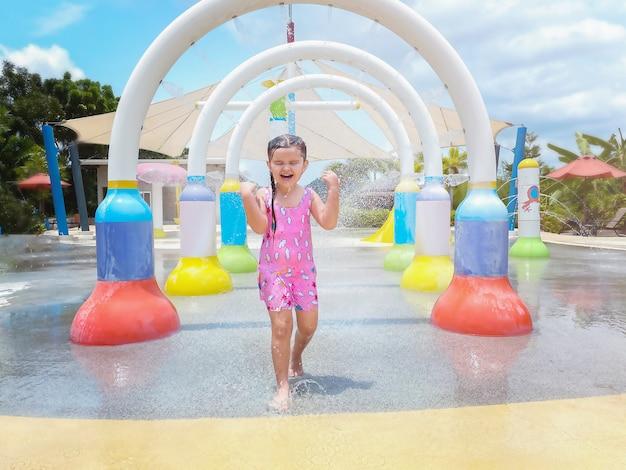 Девушка бежит под брызгами фонтана в бассейне