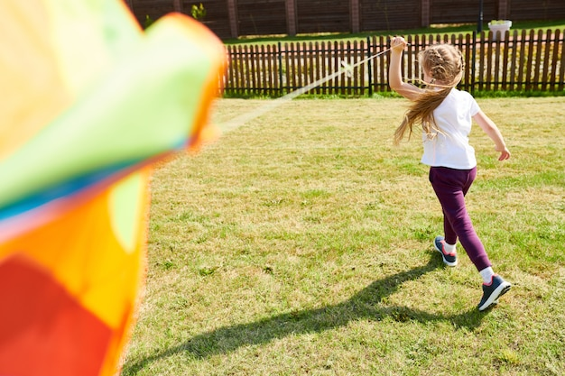 Girl running with colorful kite
