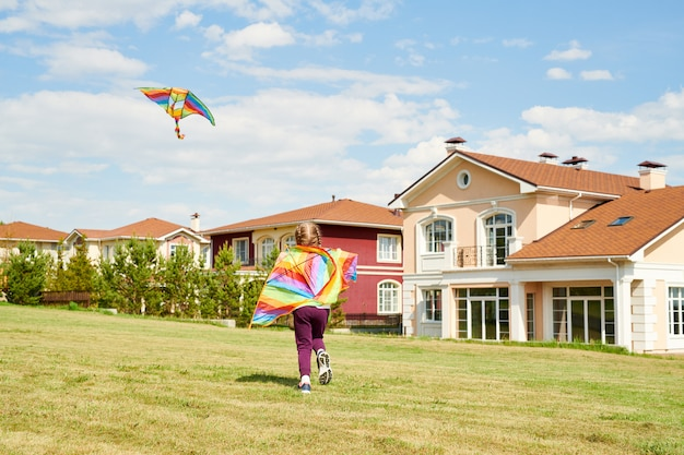 Girl running with kite